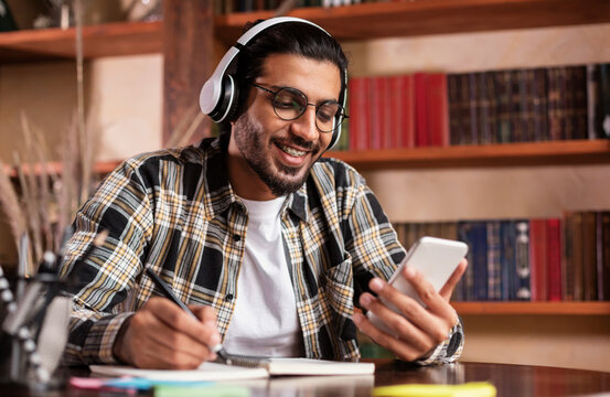 Happy Indian Student With Smartphone Learning Sitting In University Library