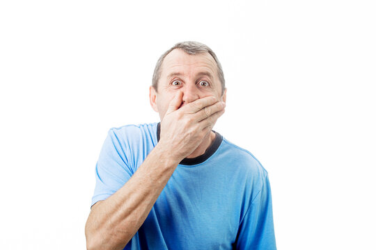 Shocked middle aged man with wide opened eyes covering his mouth with his hand isolated on white background with copy space. Surprised business middle aged worker with en astonished expression.