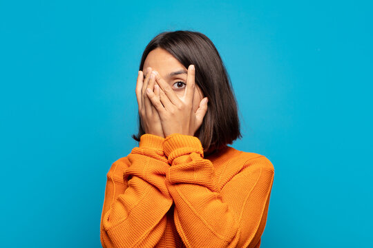 hispanic woman feeling scared or embarrassed, peeking or spying with eyes half-covered with hands