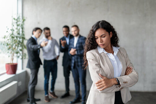 Unhappy Businesswoman Standing While Colleagues Whispering Behind Back In Office