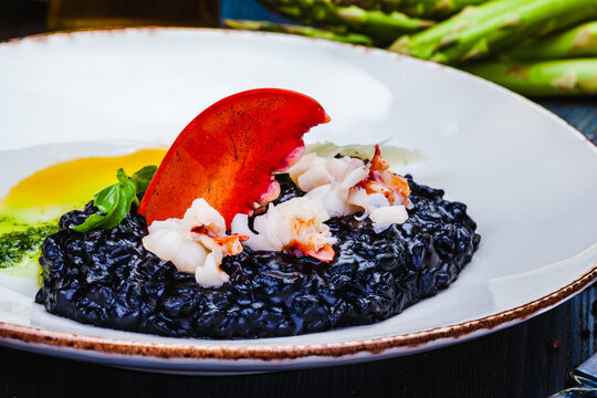 Black squid ink risotto with lobster and parmesan cheese on white plate.