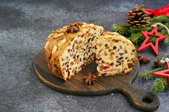 Sliced traditional Scottish Christmas Dundee fruit cake with dried fruit mix, garnished with peeled almonds on a wooden board against a dark concrete background.