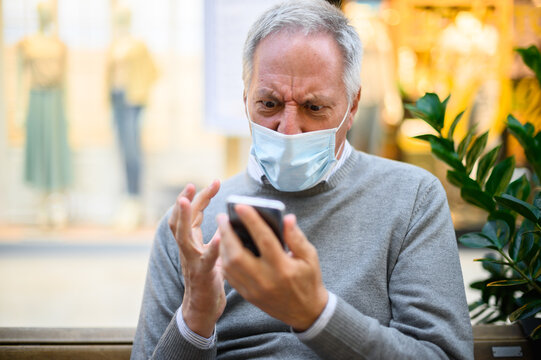 Senior man sitting on a bench and using a smartphone in a mall wearing mask and getting angry, coronavirus concept