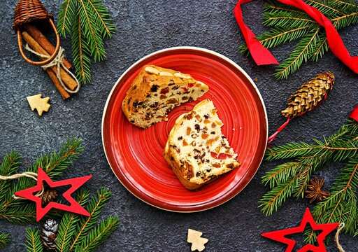 Sliced traditional Scottish Christmas Dundee fruit cake with dried fruit mix, garnished with peeled almonds on a red plate against a dark concrete background.