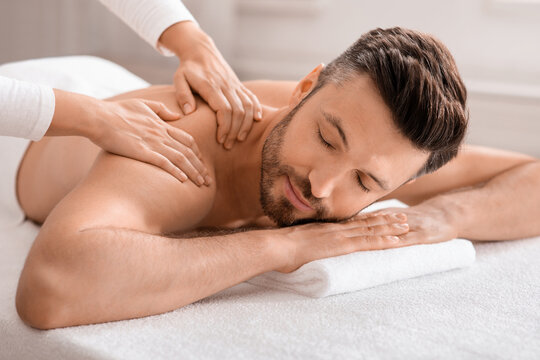 Closeup of relaxed man having body massage at spa