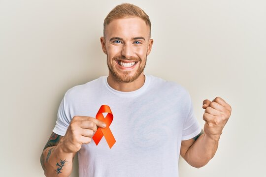 Young caucasian man holding orange ribbon for leukemia awareness screaming proud, celebrating victory and success very excited with raised arm