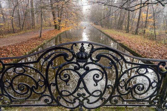 Herbstspaziergang im Schlosspark in München - Brückengeländer und Fluss im morgendlichen Nebel