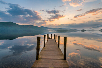 Long wooden jetty with poles leading out to lake at sunset in the Lake District, UK.