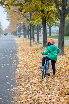 Beautiful autumn shot of a child on a bike looking at something