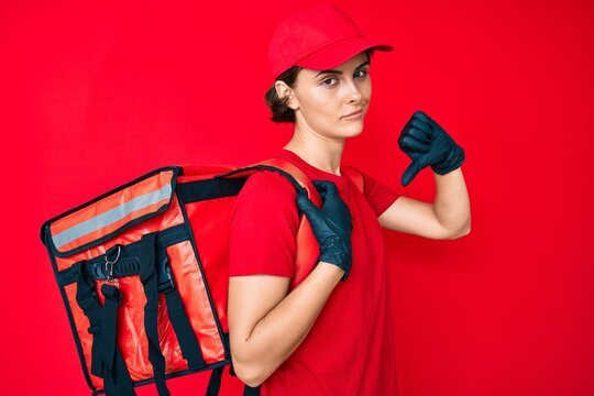 Young hispanic woman holding take away backpack with angry face, negative sign showing dislike with thumbs down, rejection concept