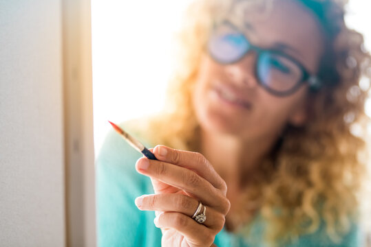 close up of beautiful woman with glasses painting a big sheet at home