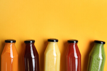 Bottles with delicious colorful juices on yellow background, flat lay. Space for text