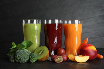Delicious colorful juices in glasses and fresh ingredients on black table