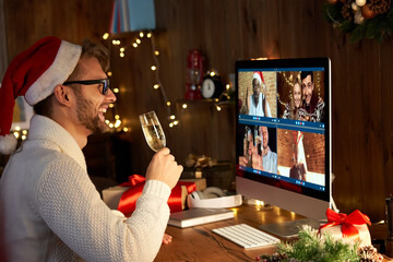 Happy young man wearing santa hat drinking champagne talking to friends on virtual video call...
