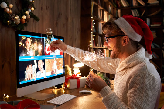 Young man wearing Christmas hat drinking champagne holding sparkler talking to friends on virtual video call celebrate Happy New Year party in distance online conference chat on pc computer at home.