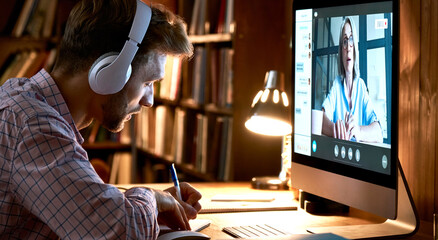 Male student wearing headphones conference video calling, watching webinar, online training class,...