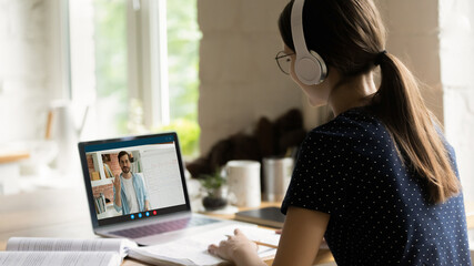 Rear back view happy young caucasian girl in headphones holding video call consultation with...