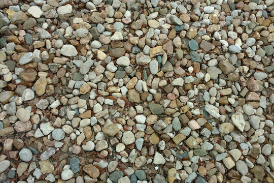 a close up view of a stone pebble rock gravel garden path backyard trail suitable for background backdrop also like a footpath walkway park featuring overhead detail textured surface pattern