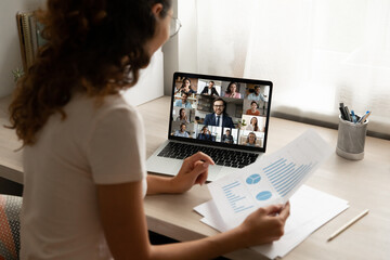 Rear back view happy young female employee working remotely at home office, holding video call...