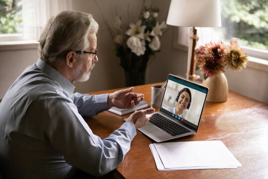 Side view focused elderly 60s businessman talking online with indian ethnicity female colleague, using computer video call application, consulting with helpline specialist, distant communication.