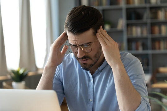 Male office employee sit at desk suffers from headache touches temples reduce pain. Thinking process try to remember important, search ideas, migraine chronic fatigue modern technology overuse concept