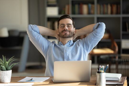 Relaxed man take break from work put hands behind head lean on comfy chair closing eyes feels serenity, enjoy fresh conditioned air in modern office, no stress, fatigue relieve at workplace concept