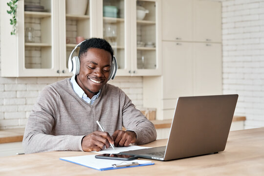 Happy african business man, black male student wearing headphones elearning on laptop computer sitting at kitchen table working from home office, learning online, studying remote training course.