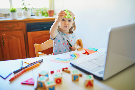 Toddler girl learning shapes in front of laptop