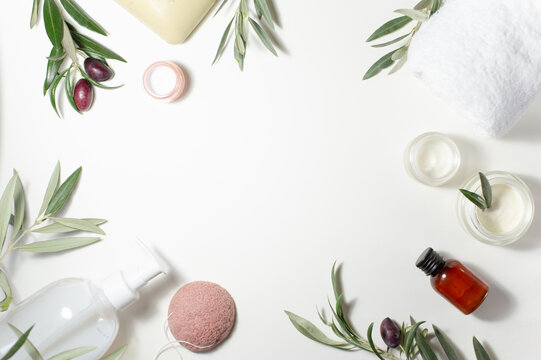 Spa and beauty. A set of cosmetics for care. Soap, cream, towel, shampoo, sponge and olive tree sprigs are arranged around the perimeter on a white background.