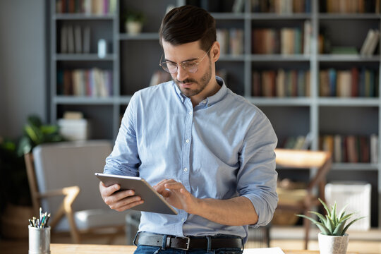 Focused serious businessman freelancer in glasses standing in modern office lean on table hold tablet device texting message to client, web surfing on-line, makes business offer to partner by e-mail
