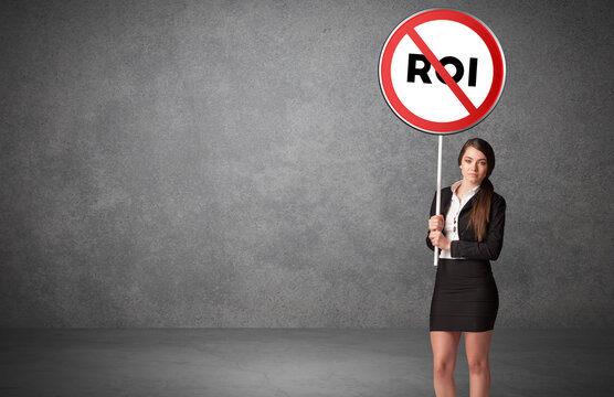 Young business person holdig traffic sign with ROI abbreviation, technology solution concept