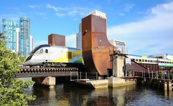 Brightline train travels north through the Florida East Coast (FEC) Railway Bridge in downtown Fort Lauderdale, Florida, USA.