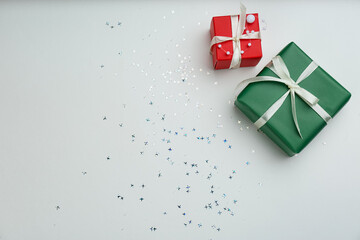 Christmas gift boxes with shiny confetti on light background, flat lay. Space for text