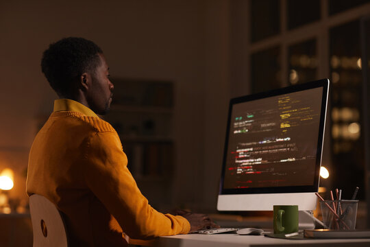 Side view portrait of contemporary African-American man looking at computer screen while working late at night writing code, copy space