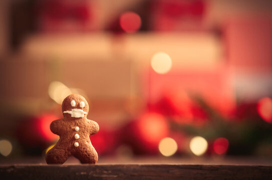 Gingerbread man on table with Christmas gifts on background