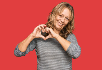 Middle age blonde woman wearing casual clothes smiling in love showing heart symbol and shape with...