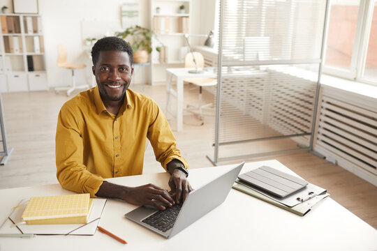 High angle portrait of smiling African-American man using laptop and looking at camera while enjoying work in minimal office interior, copy space