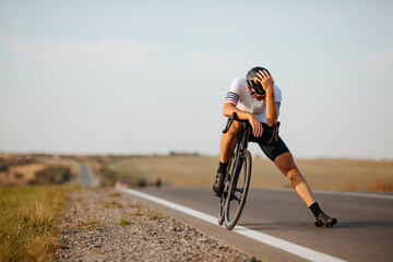 Exhausted cyclist relaxing on road after long riding