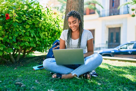 Young african american student woman smiling happy using computer laptop sitting on the grass at the university campus