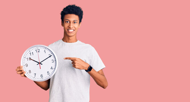 Young african american man holding big clock smiling happy pointing with hand and finger