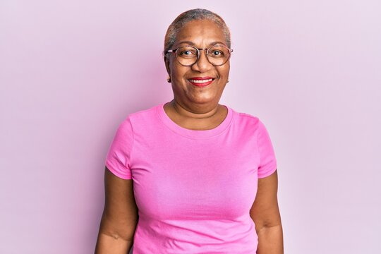 Senior african american woman wearing casual clothes and glasses looking positive and happy standing and smiling with a confident smile showing teeth