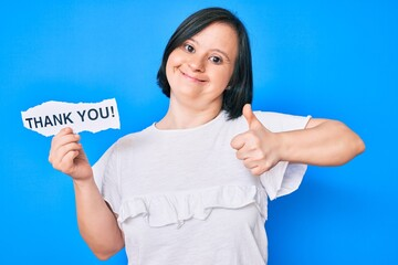 Brunette woman with down syndrome holding thank you paper smiling happy and positive, thumb up...