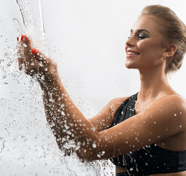 Sexy blonde enjoying water stream in studio