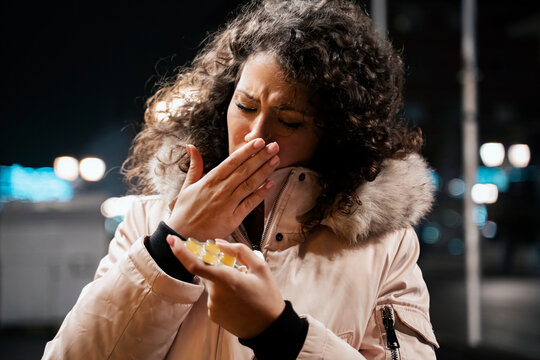 Young woman in winter jacket coughing outdoors and holding medicine , or throat lozeng