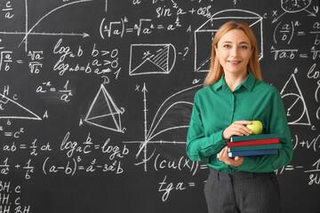 Mature maths teacher near blackboard in classroom
