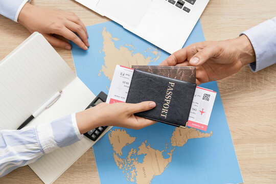 Travel agent giving client documents for future trip in office