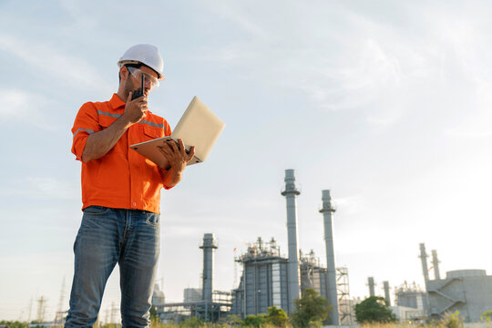 male caucasian engineer technician Industrial workers wearing safty uniform with walkie-talkie and laptop working inspection in a power plant background