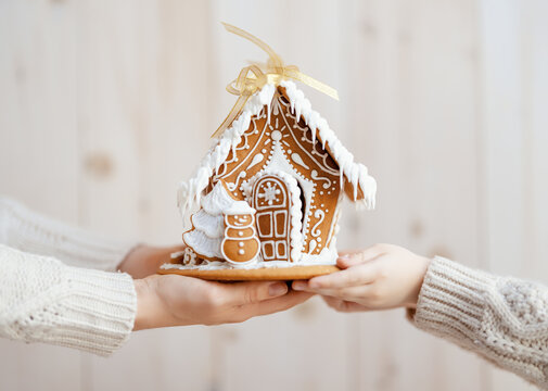 Adult and child are holding gingerbread house.