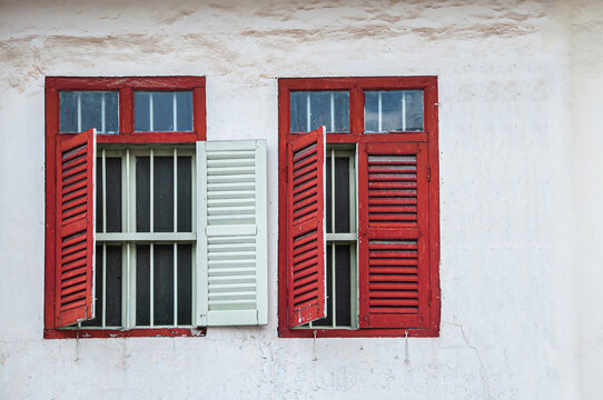 Old red window on white concrete wall