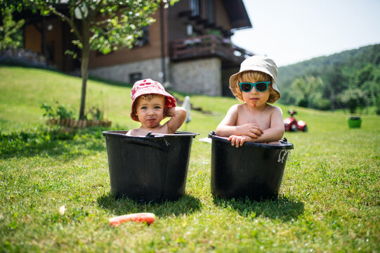 Topless small boy and girl with hats in buckets outdoors in summer garden.